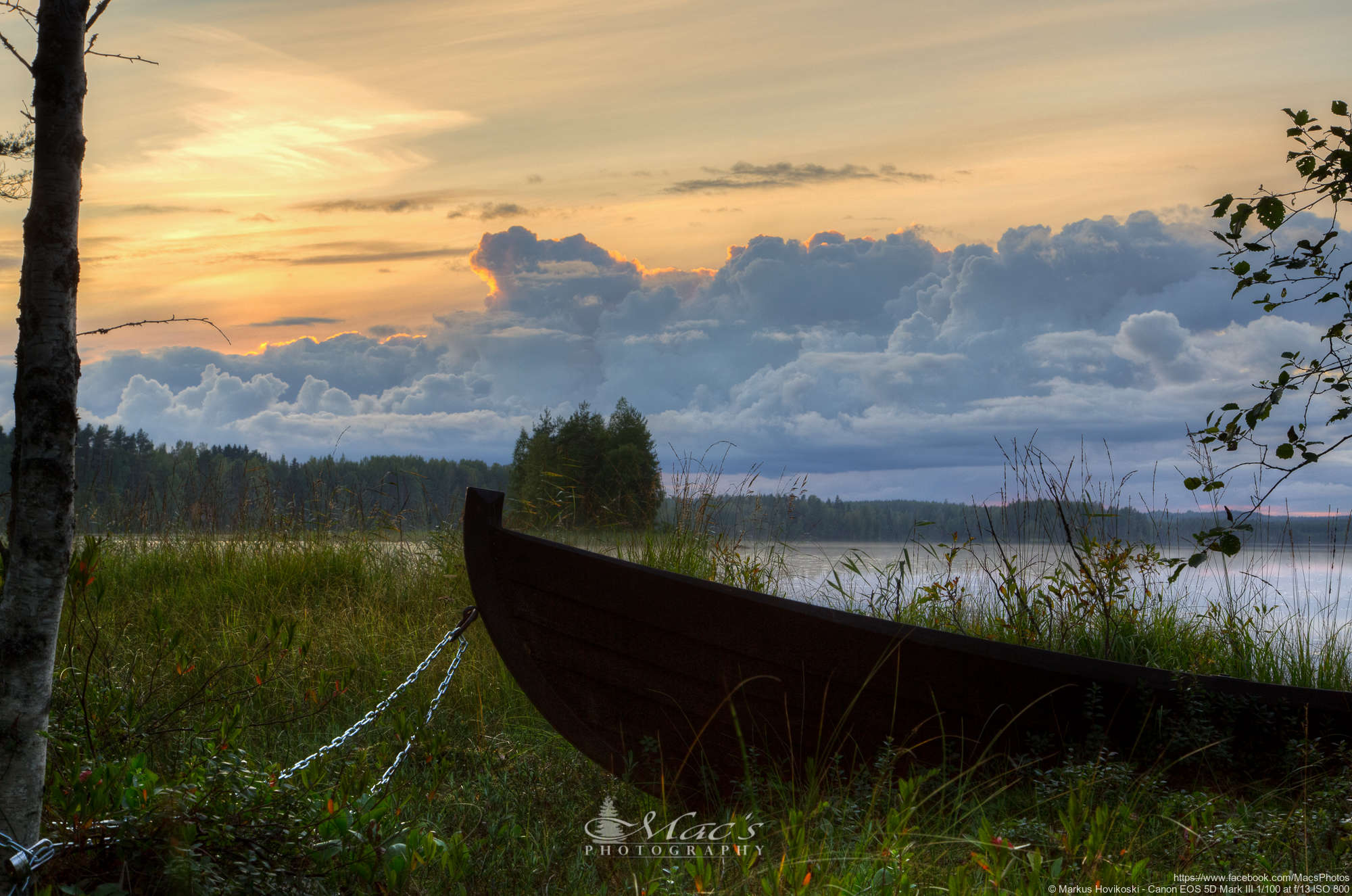 An old boat chained to a tree with stormy clouds and fall sunset in Finland
